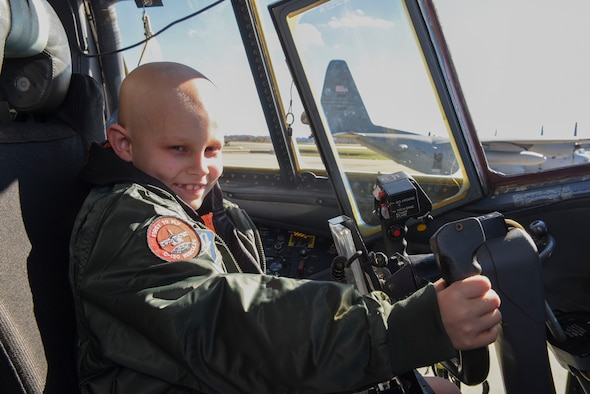 """Drew Palmer, an eight-year old battling bone cancer, holds the control wheel of a C-130 Hercules at the Pittsburgh International Airport Air Reserve Station, Pa., Nov. 4, 2015. Palmer was honored as a """"Pilot for a Day"""" and made an honorary Second Lieutenant for the day as he was able to tour the base and see what Airmen of the 911th Airlift Wing do on a daily basis. During his tour, he also visited the Navy Operational Support Center where he was made an honorary Lieutenant Commander. (U.S. Air Force photo by Staff Sgt. Joshua J. Seybert)"""