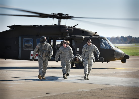 Airmen from the 911th Aeromedical Staging Squadron work with Soldiers from the Pennsylvania Army National Guard's 1-104th Attack Reconnaissance Battalion to safely unload injured personnel during a training exercise Nov. 8, 2015, at the Pittsburgh International Airport Air Reserve Station. 911th ASTS members trained with the National Guard Soldiers, based out of Johnstown, Pennsylvania, on an engine running on-load/off-load exercise with the Guard's UH-60 Blackhawk helicopter. (U.S. Air Force photo by Staff Sgt. Justyne Obeldobel)