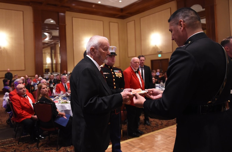 Capt. David Rubio, Company A, Marine Cryptologic Support Battalion commanding officer, passes the first slice of cake to the oldest U.S. Marine during the Marine Corps Birthday Ball Nov. 6, 2015, at the Denver Athletic Club, Denver. The ball was held in honor of the Marine Corps' 240th birthday, complete with a guest speaker, dinner and dancing. (U.S. Air Force photo by Airman 1st Class Samantha Meadors/Released)