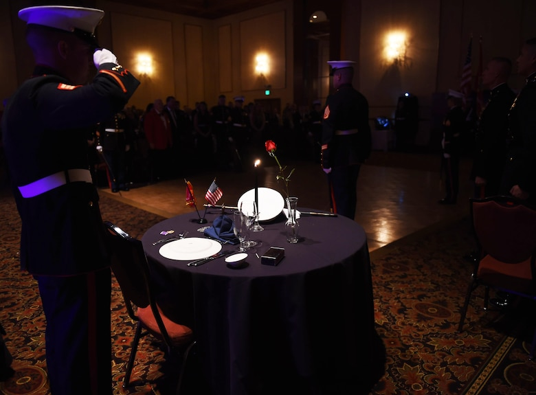 A U.S. Marine renders a salute to the Prisoner of War/Missing in Action table during the Marine Corps Birthday Ball Nov. 6, 2015, at the at the Denver Athletic Club, Denver. The ball was held in honor of the Marine Corps' 240th birthday, complete with a guest speaker, dinner and dancing. (U.S. Air Force photo by Airman 1st Class Samantha Meadors/Released)
