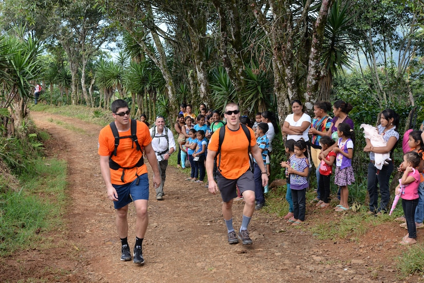 Two U.S. military members based out of Soto Cano Air Base, Honduras, hike food and supplies to those in need during Chapel Hike 64, Oct. 31, 2015. Chapel Hikes take place every six weeks and provide community outreach by bringing much needed food and supplies to the less fortunate. (U.S. Air Force photo by Senior Airman Westin Warburton/Released)