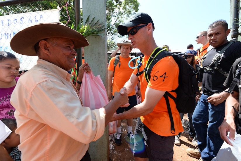 U.S. Air Force Lt. Col. James Trachier, deputy commander Joint Task Force Bravo, hands a local man a bag of food and supplies during Chapel Hike 64, Comayagua, Honduras, Oct. 31, 2015. Chapel Hikes take place every six weeks and provide community outreach by bringing much needed food and supplies to the less fortunate. (U.S. Air Force photo by Senior Airman Westin Warburton/Released)