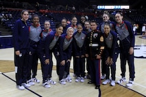 Gunnery Sgt. Manuel Beltran poses for a photo with the University of Connecticut's Huskies, Woman's Basketball Team, at the Harry A. Gampel Pavilion, Nov. 8. Beltran attend a Huskies game to present the team's coach, Geno Auriemma, as the 2015 United States Marine Corps/WBCA NCAA Division I Regional Coach of the Year. (Official Marine Corps Photo by Staff Sgt. Richard Blumenstein)