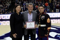 (Center) Geno Auriemma, the University of Connecticut's Woman's Basketball Coach, is awarded the 2015 United States Marine Corps/WBCA NCAA Division I Regional Coach of the Year, at the Harry A. Gampel Pavilion, Nov. 8. Gunnery Sgt. Manuel Beltran, right, and Danielle M. Donehew, left, the executive director for WBCA, presented Auriemma the award. The award is meant to recognize a coach for exemplary accomplishments throughout the year. (Official Marine Corps Photo by Staff Sgt. Richard Blumenstein)