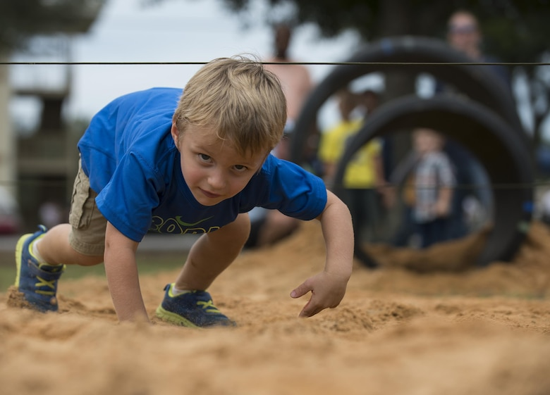 Gavin Sutphen low crawls through the obstacle course during the Duke Field Wing Day event Nov. 7.  The 919th Special Operations Wing sets aside a special day each year to show appreciation for its reservists and their family members. Events included music, sports, children's games, etc. (U.S. Air Force photo/Tech. Sgt. Jasmin Taylor)