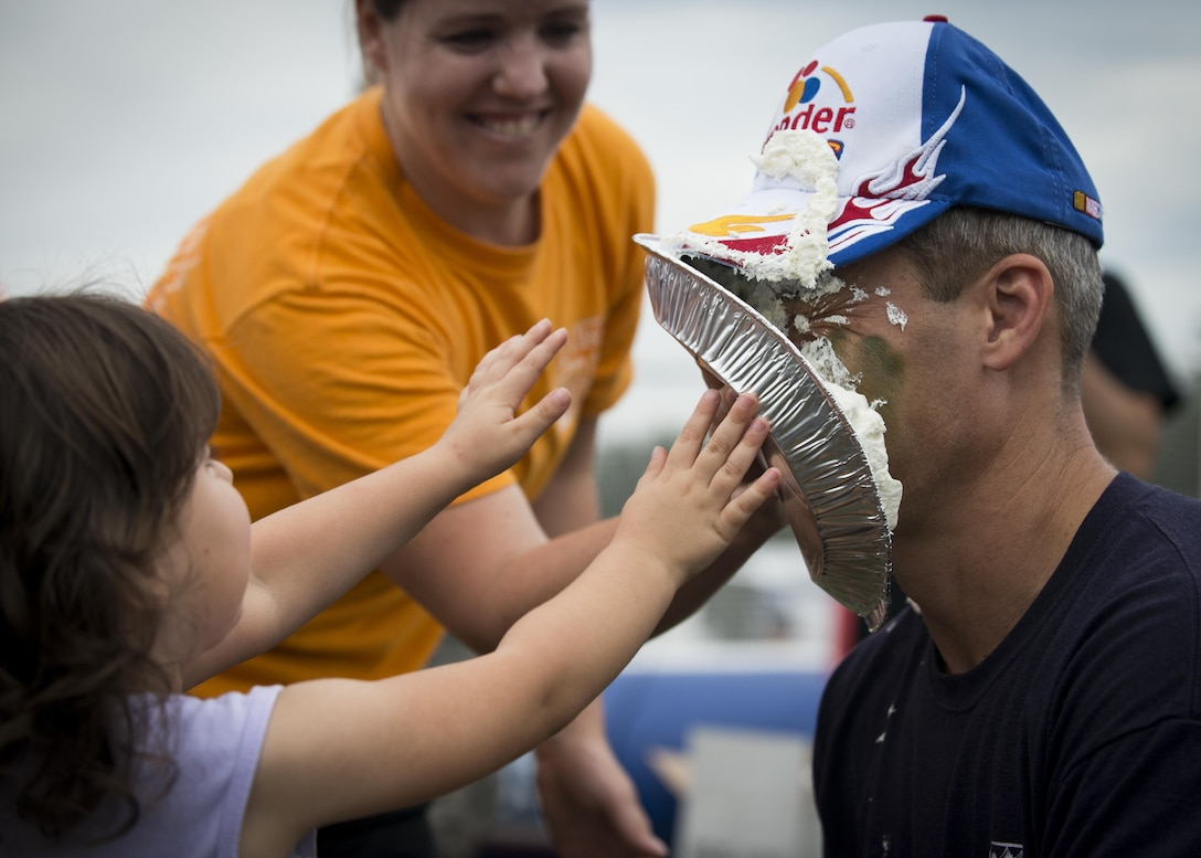 Peyton Roszkowski throws a pie in Col. Robert Bruckner, 919th Special Operations Wing Vice commander during the Duke Field Wing Day event Nov. 7.  The 919th SOW sets aside a special day each year to show appreciation for its reservists and their family members. Events included music, sports, children's games, etc. (U.S. Air Force photo/Tech. Sgt. Jasmin Taylor)