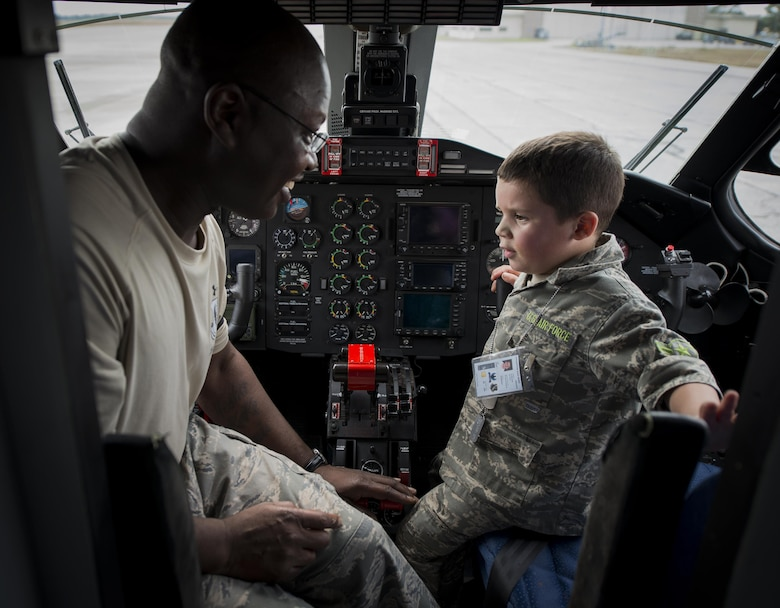 "Tech. Sgt. Sedrick Dottin, 919th Special Operations Aircraft Maintenance Squadron, and Kekoa Lee tours a C-145 during the Duke Field Operation Hero event Nov. 7. The event was a mock deployment exercise for 919th Special Operations Wing children. The exercise started with the kids receiving orders before deploying to the 919th Special Operations Logistics Readiness Squadron building. The ""little deployers"" were issued fake military ID cards, dog tags, and immunizations. (U.S. Air Force photo/ Tech. Sgt. Jasmin Taylor)"