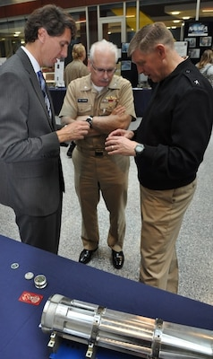 Hamish Malin, NSWCDD electromagnetic railgun projectile designer, briefs NSWC Commander Lorin Selby (right) and Navy Warfare Centers Chief of Staff Capt. Randell Dykes about the challenge of gun-hardening delicate electronics in his efforts to turn projectiles into guided missiles.