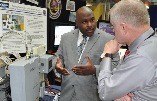 Naval Surface Warfare Center Dahlgren Division (NSWCDD) chemist Tim Anthony explains the Navy's shipboard chemical warfare agent detector, called the Improved Point Detection System - Life cycle Replacement, at the NSWCDD Briefing and Technical Demonstration held at Naval Sea System Command headquarters, Nov. 3. The Navy has installed the system  - designed to quickly alert warfighters to the presence of chemical warfare agents - on 50% of all active guided missile destroyers and cruisers, aircraft carriers, large and small deck amphibious ships, littoral combat ships and dry cargo/ammunition ships with plans to be completed by the end of 2019.