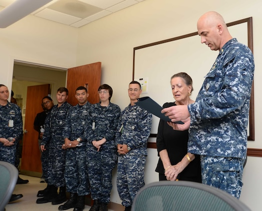 Sailors and civilian personnel look on as Cmdr. Raymond Bristol, officer-in-charge, Naval Branch Health Clinic Albany, presents Fran Quinn,  health benefits advisor, NBHC Albany, with commendations honoring her for 55 years of federal service in a retirement ceremony at Marine Corps Logistics Base Albany, Nov. 4. Quinn has spent the last 48 years of her extensive civil service career at NBHC Albany.
