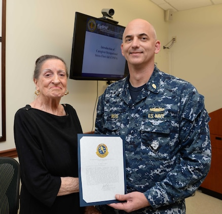 Cmdr. Raymond Bristol, officer-in-charge, Naval Branch Health Clinic Albany, presents Fran Quinn, health benefits advisor, NBHC Albany, with commendations and gifts during a retirement ceremony at the clinic aboard Marine Corps Logistics Base Albany, Nov. 4. Quinn was honored by personnel and well-wishers for her 55 years of federal service, 48 of which were spent at NBHC Albany.
