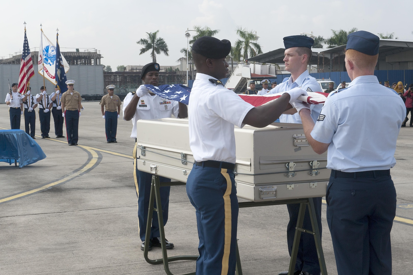 A joint service team prepares to drape an American flag over a casket during a repatriation ceremony at Subang Air Base, Malaysia, Nov. 5, 2015. The 15-member team comprised of members of the Defense POW/MIA Accounting Agency as well service members from U.S. Army Pacific and Pacific Air Force Command, was sent from Hawaii to honor the remains of a fallen service member who paid the ultimate sacrifice when his plane went down over Malaysia in 1945. The ceremony signifies the transfer of the remains from Malaysia back to the U.S. where the service member can be ultimately identified and returned home. The ceremony marks the first of its kind between the two countries. The mission of the Defense POW/MIA Accounting Agency is to provide the fullest possible accounting for our missing personnel to their families and the nation. (U.S. Air Force photo by Staff Sgt. Brian J. Valencia)