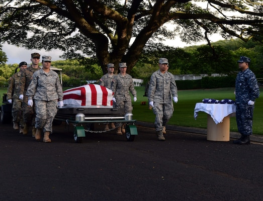 Members of the Defense POW/MIA Accounting Agency (DPAA) march alongside a disinterred casket holding the remains of unknown USS Oklahoma service members during a disinterment ceremony at the National Memorial Cemetery of the Pacific in Honolulu, Nov. 5, 2015. Today's ceremony was the final disinterment for the USS Oklahoma. The DPAA mission is to provide the fullest possible accounting for our missing personnel to their families and the nation. (U.S. Air Force photo by Staff Sgt. La'Shanette Garrett/Released)