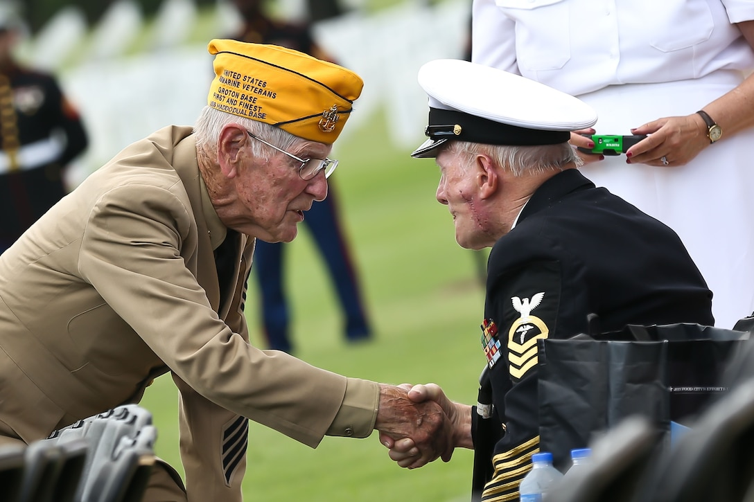 Retired Senior Chief Electronics Technician Lee Rogers, 84, and retired Chief Hospital Corpsman Frank Lowe, 95, shake hands before Marine Staff Sgt. David Wyatt's funeral July 24, 2015, at the Chattanooga National Cemetery in Tennessee. Rogers joined the Navy during the Korean War, and Lowe fought at Guadalcanal during World War II.