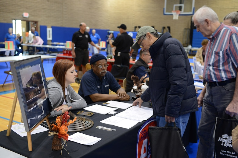 Brittney Whiting, 56th Force Support Squadron recreation assistant, and Don Harris, 56th FSS auto hobby shop manager, talk with a retiree about the services they offer during Retiree Appreciation Day at Luke Air Force Base, Arizona, Nov. 7, 2015. There were several base volunteers in attendance to support the retirees from various units. (U.S. Air Force photo by Senior Airman James Hensley)