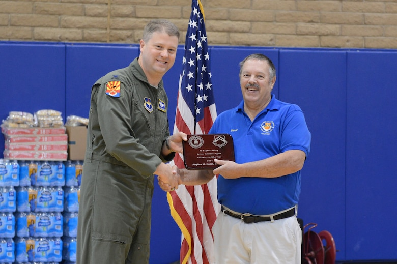 Col. David Shoemaker, 56th Fighter Wing vice commander, hands the retiree activities office volunteer of the year plaque to Stephen Smith, Retired Activities Office civilian, during Retiree Appreciation Day at Luke Air Force Base, Arizona, Nov. 7, 2015. (U.S. Air Force photo by Senior Airman James Hensley)