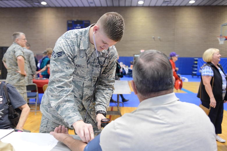 Senior Airman Kyle King, 56th Medical Operations Squadron medical technician, checks the blood pressure on a retiree during Retiree Appreciation Day at Luke Air Force Base, Arizona, Nov. 7, 2015. The checkup was free and was designed to educated retirees on benefits and services available to them. Retirees were also afforded the opportunity to receive the influenza vaccine. (U.S. Air Force photo by Senior Airman James Hensley)