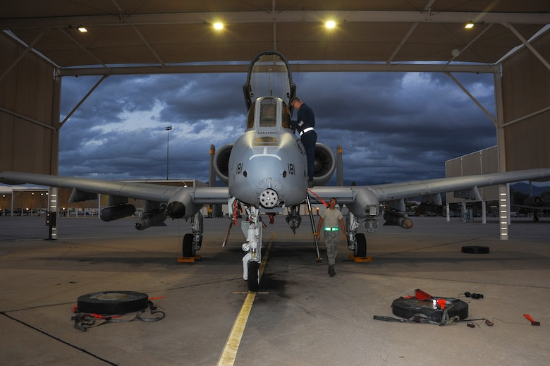 Two 355th Aircraft Maintenance Squadron A-10C Thunderbolt II crew chiefs prepare to cover an A-10 and extract its pilot at Davis-Monthan Air Force Base, Ariz., Nov. 4, 2015.  Crew chiefs cover the jet's intake to prevent foreign object damage to the engines. (U.S. Air Force photo by Airman 1st Class Ashley N. Steffen/Released)