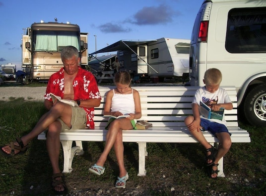 The Waltermire family sits and reads on a bench at an RV park in Key West, Fla., during a family trip in 2005.