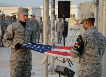 Members of the Al Udeid Air Base, Qatar Honor Guard fold the U.S. flag during a retreat ceremony at the base Nov. 11 in observance of Veterans Day. The retreat ceremony was held to honor America's veterans past and present. (U.S. Air Force photo by Tech. Sgt. James Hodgman/Released)