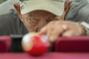 Vietnam veteran Jim Alderman lines up a shot during a game of pool in the recreation room at the inpatient post-traumatic stress disorder clinic at the Bay Pines Veterans Affairs Medical Center in Bay Pines, Fla., Oct. 30, 2015. DoD photo by EJ Hersom