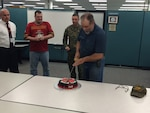 Shawn Searer, DLA Distribution Susquehanna, Pa., maintenance supervisor, carries on Marine Corps tradition by cutting the cake as the most senior Marine at the organization.