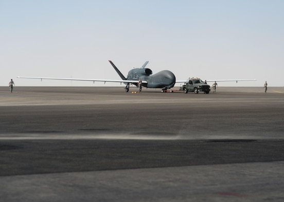 U.S. Airmen assigned to the 380th Expeditionary Aircraft Maintenance Squadron, recover an EQ-4 Global Hawk unmanned aircraft at an undisclosed location in Southwest Asia, Nov. 11, 2015. The EQ-4 Global Hawk nicknamed the 'Workhorse' by local maintainers, completed its 500th sortie on Veterans Day. (U.S. Air Force photo by Tech. Sgt. Frank Miller/Released)
