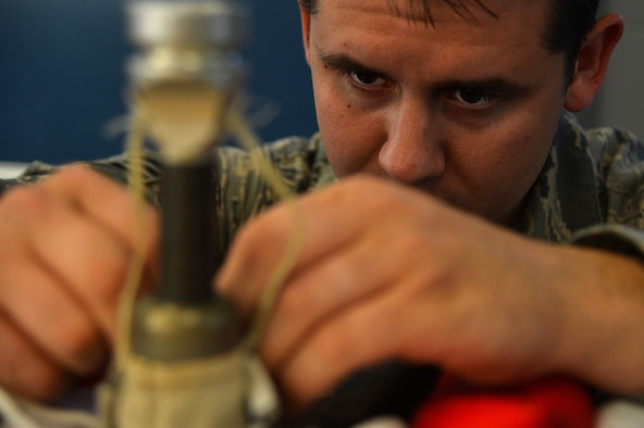Senior Airman Kyle Burroughs, a 20th Operations Support Squadron aircrew flight equipment specialist, secures a backup firing lanyard to a mortar tube sleeve at Shaw Air Force Base, S.C., Oct. 20, 2015. The firing lanyards ensure proper deployment of the parachute canopy. (U.S. Air Force photo/Senior Airman Michael Cossaboom)