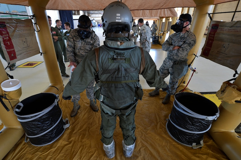 Airmen assigned to the 20th Operations Support Squadron mitigate a pilot during decontamination training at Shaw Air Force Base, S.C., Oct. 23, 2015. During the training, pilots and aircrew flight equipment Airmen practiced the actions they would take if a pilot became contaminated during flight. (U.S. Air Force photo/Senior Airman Michael Cossaboom)