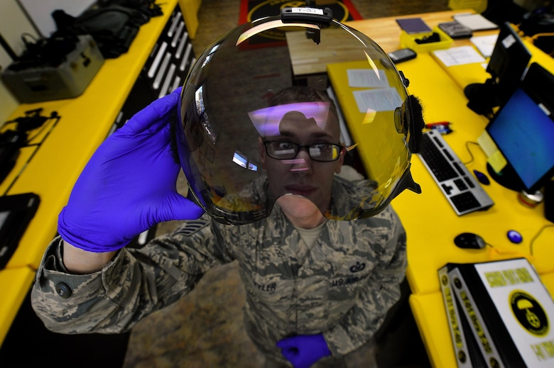 Staff Sgt. Anthony Tyler, a 20th Operations Support Squadron aircrew flight equipment specialist, inspects the visor of a pilot's helmet at Shaw Air Force Base, S.C., Oct. 21, 2015. Tyler has to inspect the visor for scratches and damage to ensure the pilots vision isn't obscured during flight. (U.S. Air Force photo/Senior Airman Michael Cossaboom)