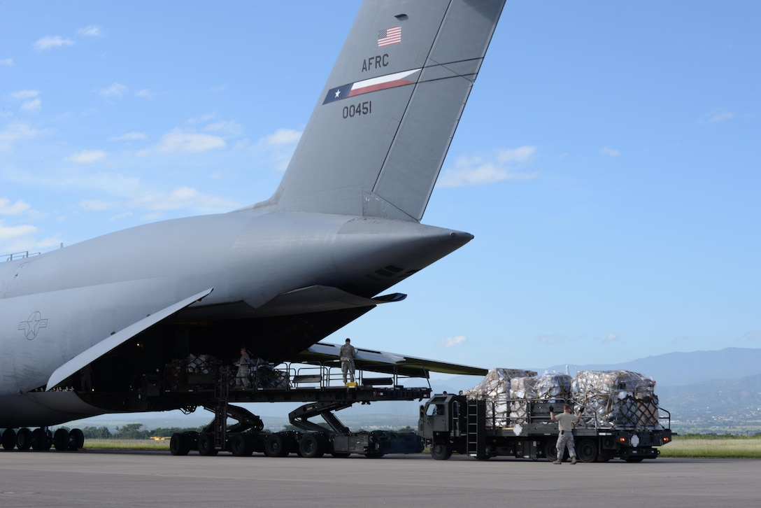 Members of the 612th Air Base Squadron unload humanitarian supplies from a C-5 Galaxy, assigned to the 68th Airlift Squadron, on Soto Cano Air Base, Honduras, Nov. 9, 2015. The C-5 delivered 23,415 pounds of cargo made possible by the Denton Program, which allows the use of extra space on U.S. military cargo aircraft to transport humanitarian assistance materials donated by nongovernment organizations, international organizations and private voluntary organizations for humanitarian relief. (U.S. Air Force photo/Senior Airman Westin Warburton)