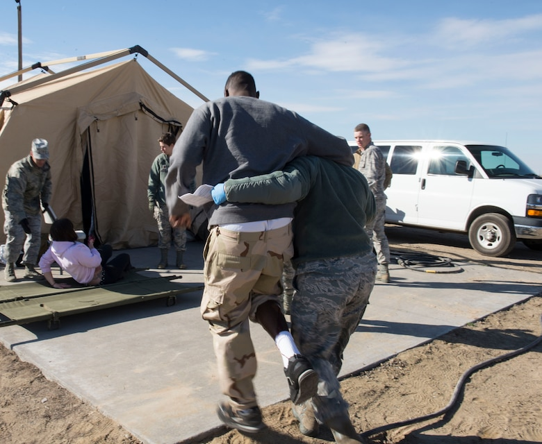 Capt. Amanda Roby, operating room nurse with the 141st Medical Group helps Airman 1st Class Kevin Joseph, aerospace medical technician from the 366th Medical Operations Squadron, walk to a safe place for his simulated evaluation at Mountain Home Air Force Base, Idaho, Nov. 5, 2015. Joseph volunteered to act as an injured patient during the Gunfighter Flag 16-1 exercise. (U.S. Air Force photo by Airman 1st Class Jessica H. Evans/RELEASED)