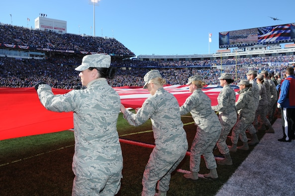 Military personnel from the Western New York community hold a flag during the national anthem on Nov. 8, 2015 at Ralph Wilson Stadium in Orchard Park, N.Y. The ceremony also included a pregame introduction and a flyover of a C-130 Hercules from the 328th Airlift Squadron. (U.S. Air Force photo by Staff Sgt. Matthew Burke)