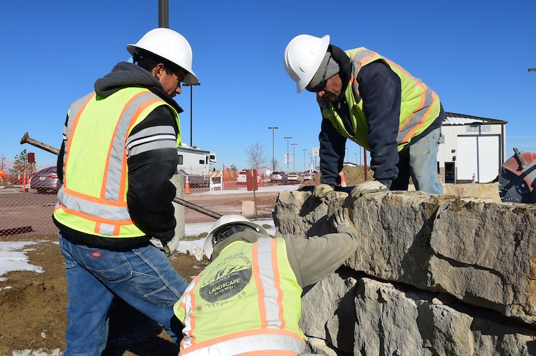 Workers from Mountain Splendor Service Inc. orient rocks to form a platform Nov. 12, 2015, at Buckley Air Force Base, Colo. The rocks are being installed to provide a stable platform for a new entrance sign to Buckley AFB at the Mississippi Gate. (U.S. Air Force photo by Airman Luke W. Nowakowski/Released)