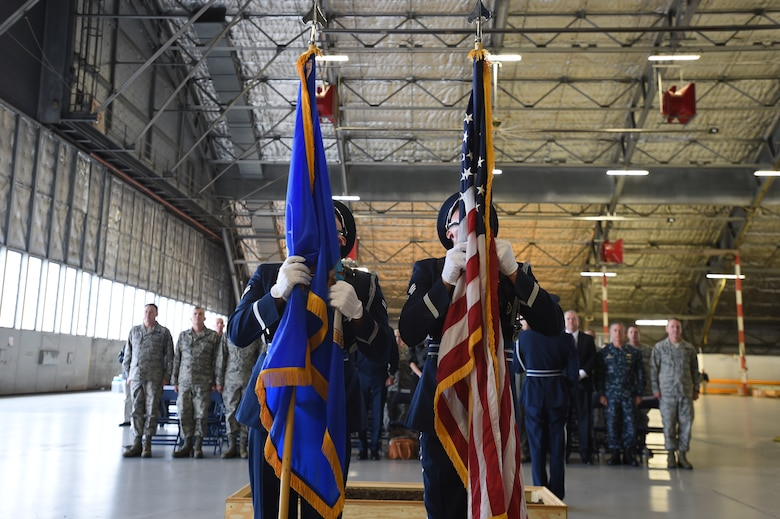 Team Andrews Airmen stand at attention while base honor guard dress the U.S. and Air Force flags during a ground breaking ceremony for the 811 Operations Group at Joint Base Andrews, Md., Nov. 12, 2015. The new facility will provide space for mission planning, briefing, training, flight simulation, operations and administration. (U.S. Air Force photo by Senior Airman Joshua R. M. Dewberry/Released)
