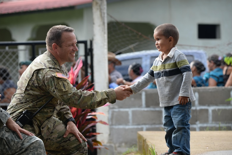 U.S. Army Capt. John Dills, Joint Task Force-Bravo tactical officer in charge, shakes hands with a boy during a medical readiness training exercise in San Jose De Rio Pinto, Honduras, Nov. 12, 2015. The MEDRETEs JTF-Bravo supports provide military members with essential training in austere locations and helps build local community relations in the host country. (U.S. Air Force Photo by Senior Airman Westin Warburton/Released)