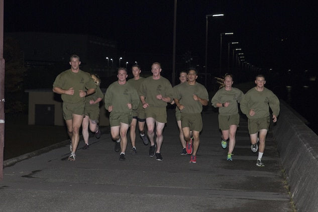 Sgt. Adrian Nanez, kennel master at the Provost Marshals Office and Cpl. Rachael Davis, military dog handler at PMO, along with Marines from Headquarters and Headquarters Squadron participate in a Marine Corps birthday relay run to commemorate the Marine Corps' 240th birthday at Marine Corps Air Station Iwakuni, Japan, Nov. 9, 2015. Service members ran a total of 240 miles, one mile for each year the Marine Corps has existed. Bystanders shouted words of encouragement as Marines and Sailors jogged by.