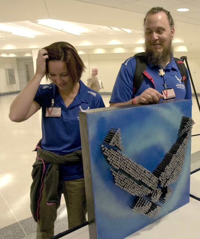Former Staff Sgt. Gregory Miller, right, and his wife Heather share a laugh while he shows his mixed media pieces during a healing arts event Nov. 12 at the Pentagon. Miller and other wounded military members were recognized for their work as part of a healing arts program created by the Defense Department and the National Endowment for the Arts to offer art therapy to recovering troops. (U.S. Air Force photo/Sean Kimmons)