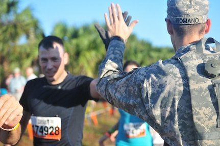 Spc. Rafaello Romano, with the 377th Theater Sustainment Command, high fives a Tough Mudder competitor at the start line of the Central Florida Tough Mudder in Palm Bay, Fla., Nov. 7. The Tough Mudder brings people together to engage in a series of challenges that not only pushes participants to their physical limits, but also tests their mental grit to get through the obstacles. (U.S. Army Reserve Photo by Sgt. Bethany L. Huff)