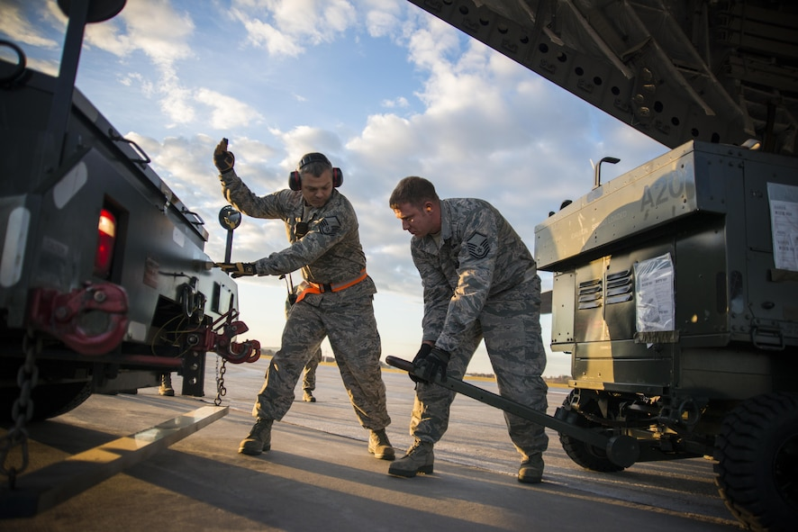Master Sgts. John Brownell and Neil Allison of the 158th Fighter Wing unload cargo from a C-17 Globemaster III at Burlington International Airport, Vt., Nov. 3, 2015. This was the final plane to return from the theater support package the Vermont Air National Guard supported. (U.S. Air National Guard photo/Airman 1st Class Jeffrey Tatro)