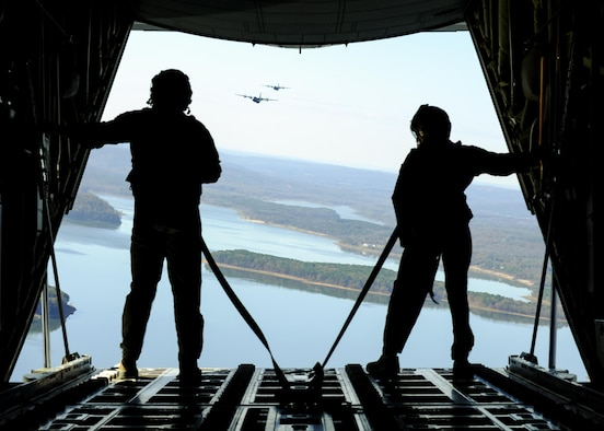 Airman Austin Metzler and Senior Airman Sean Zeringue, both C-130J Super Hercules loadmasters with the 61st Airlift Squadron, stand on the loading ramp of a C-130J during a training flight Nov. 10, 2015, above central Arkansas. The 19th Airlift Wing at Little Rock Air Force Base, Ark., is part of the Air Mobility Command and provides the Defense Department the largest C-130 fleet in the world. (U.S. Air Force photo/Senior Airman Harry Brexel)