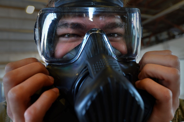 Airman 1st Class Kyle Denzine, a 20th Operations Support Squadron aircrew flight equipment specialist, checks the seal of his gas mask at Shaw Air Force Base, S.C., Oct. 23, 2015. Denzine, along with other AFE Airmen, practiced the actions they would take in the event a pilot needs to be decontaminated upon his return to base. (U.S. Air Force photo/Senior Airman Michael Cossaboom)