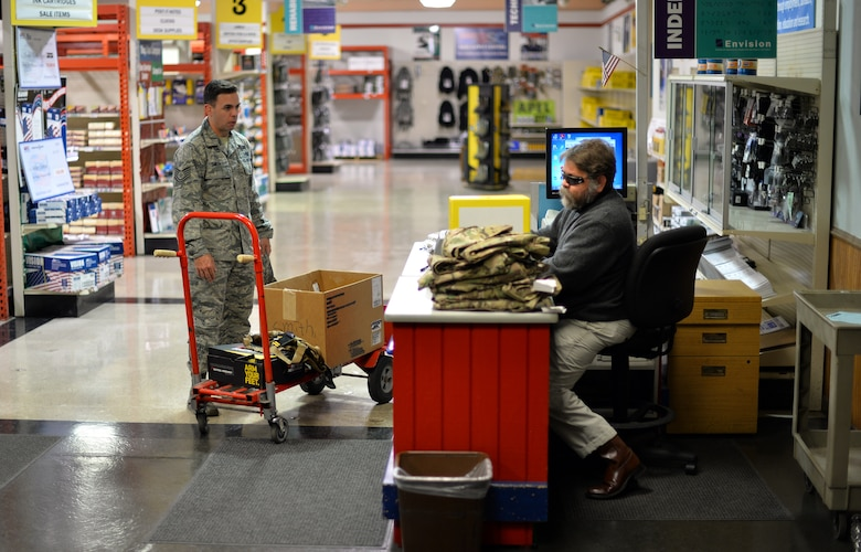 Mike Melichar rings up deployment items for Tech. Sgt. John Smith, a contracting officer in the 55th Contracting Squadron, Nov. 9, 2015 at the Envision Xpress store, Offutt Air Force Base, Neb. Melichar worked for a tiling company prior to taking the job at Envisoin. (U.S Air Force photo by Josh Plueger)