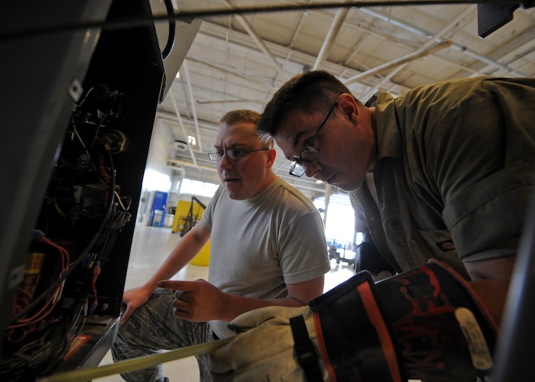 Senior Airmen James Copeland, left, and Joshua Farr, 22nd Maintenance Squadron aerospace ground equipment flight journeymen, check the voltage of a capacitor in a flood light cart, Nov. 5, 2015, at McConnell Air Force Base, Kan. The AGE flight provides the rest of the 22nd Maintenance Group with the equipment needed to troubleshoot any issues on the KC-135 Stratotanker that requires power or heating while on the ground. (U.S. Air Force photo/Senior Airman Victor J. Caputo)