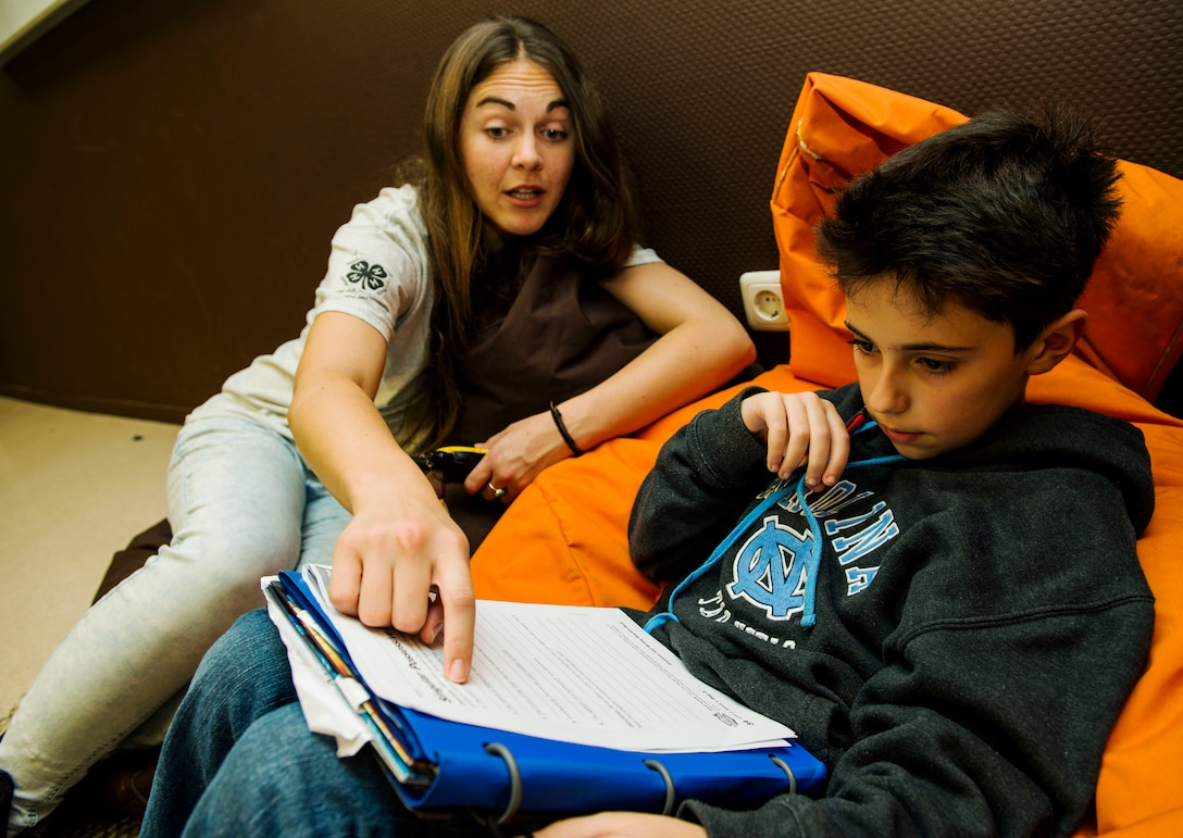 Brianna Johnston, 52nd Force Support Squadron School Age Care Program Power Hour staff member, left, assists Jackson Sansosti, right, with homework during the Power Hour in the School Age Program building at Spangdahlem Air Base, Germany, Nov. 10, 2015. The SACP staff guides students from the ages of eight to 12 on homework and other school-related subjects. (U.S. Air Force photo by Airman 1st Class Timothy Kim/Released)