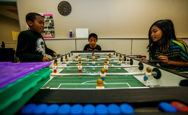 Jayden Johnson, left, Augustin Stehley, center, and Jhen Li Bangi play a game of foosball during the Power Hour in the School Age Program building at Spangdahlem Air Base, Germany, Nov. 10, 2015. The facility contains various rooms designed to allow young students to socialize, explore their interests and play together. (U.S. Air Force photo by Airman 1st Class Timothy Kim/Released)