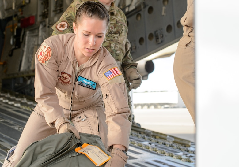 Senior Airman Beverly Spencer, 10th Expeditionary Aeromedical Evacuation Flight technician, loads a bag onto a C-17 Globemaster III Nov. 10, 2015, at Ramstein Air Base, Germany. Spencer and a crew of medical professionals departed Ramstein to retrieve and care for injured service members. (U.S. Air Force photo/Staff Sgt. Armando A. Schwier-Morales)