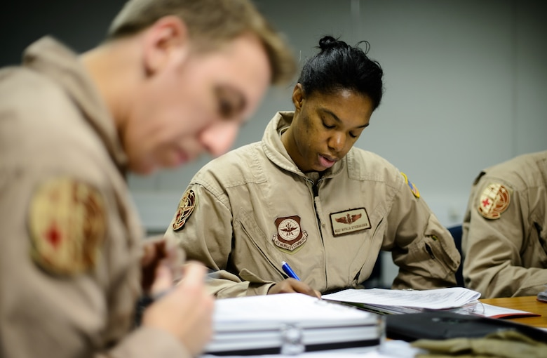 Master Sgt. Natalia Stockhausen, center, and Senior Airman Ryan Rieth, both 10th Expeditionary Aeromedical Evacuation Flight technicians, review a patient's status prior to performing an evacuation flight Nov. 10, 2015, at Ramstein Air Base, Germany. Technicians, nurses and doctors fly constantly to various areas of operation to return patients to hospitals in Germany or the U.S. for further treatment. (U.S. Air Force photo/Staff Sgt. Armando A. Schwier-Morales)