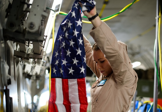 Senior Airman Beverly Spencer, 10th Expeditionary Aeromedical Evacuation Flight technician, hangs a flag inside a C-17 Globemaster III Nov. 10, 2015, at Ramstein Air Base, Germany. Spencer and crews from the 10th EAEF are deployed to Ramstein as a bridge between the deployed environment and medical facilities in the U.S. and Germany. Many Air Force aircraft conduct aeromedical evacuation, bringing the injured to the help they need. (U.S. Air Force photo/Staff Sgt. Armando A. Schwier-Morales)