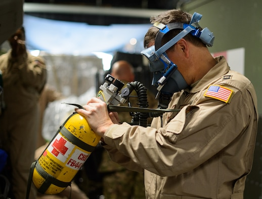Capt. Benjamin Schultze, 10th Expeditionary Aeromedical Evacuation Flight nurse, adjusts his oxygen mask Nov. 10, 2015, at Ramstein Air Base, Germany. After configuring the inside of the C-17 Globemaster III into a flying ambulance, the Airmen test their equipment to ensure they can provide the best possible treatment while flying thousands of feet in the air. The 10th EAEF is a mixture of active-duty, reserve and guard Airmen deployed to Ramstein, constantly flying to war zones to retrieve patients needing higher levels of medical care. (U.S. Air Force photo/Staff Sgt. Armando A. Schwier-Morales)